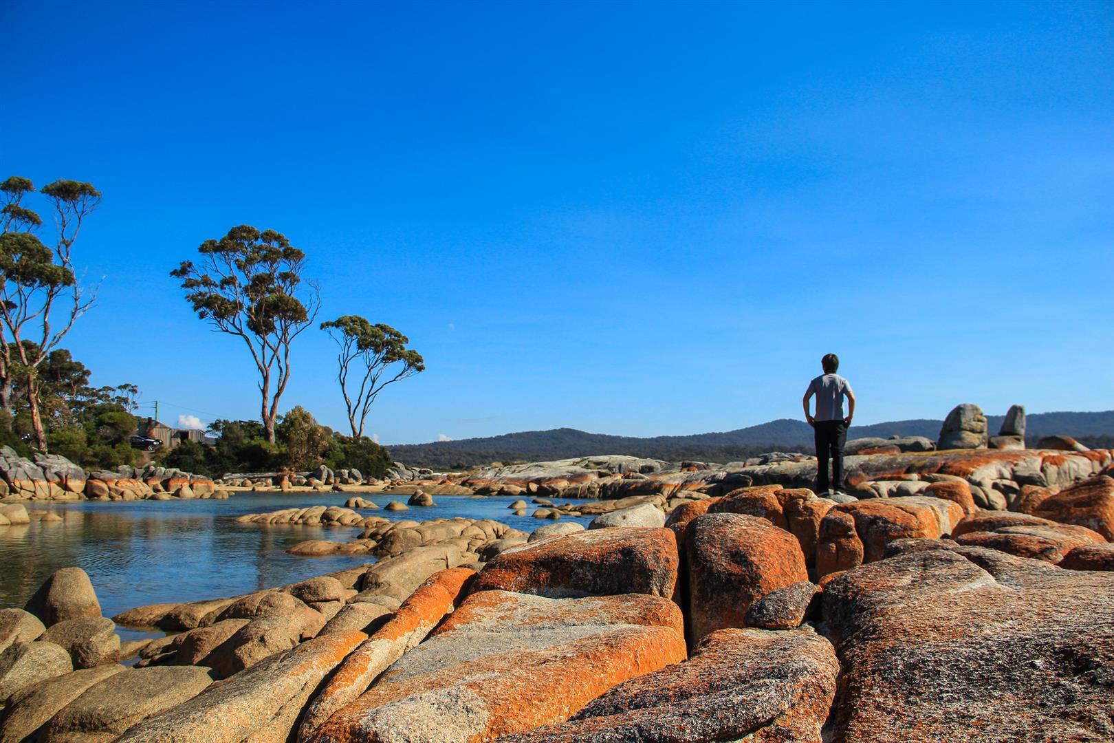 praia com mar azul e pedras laranja