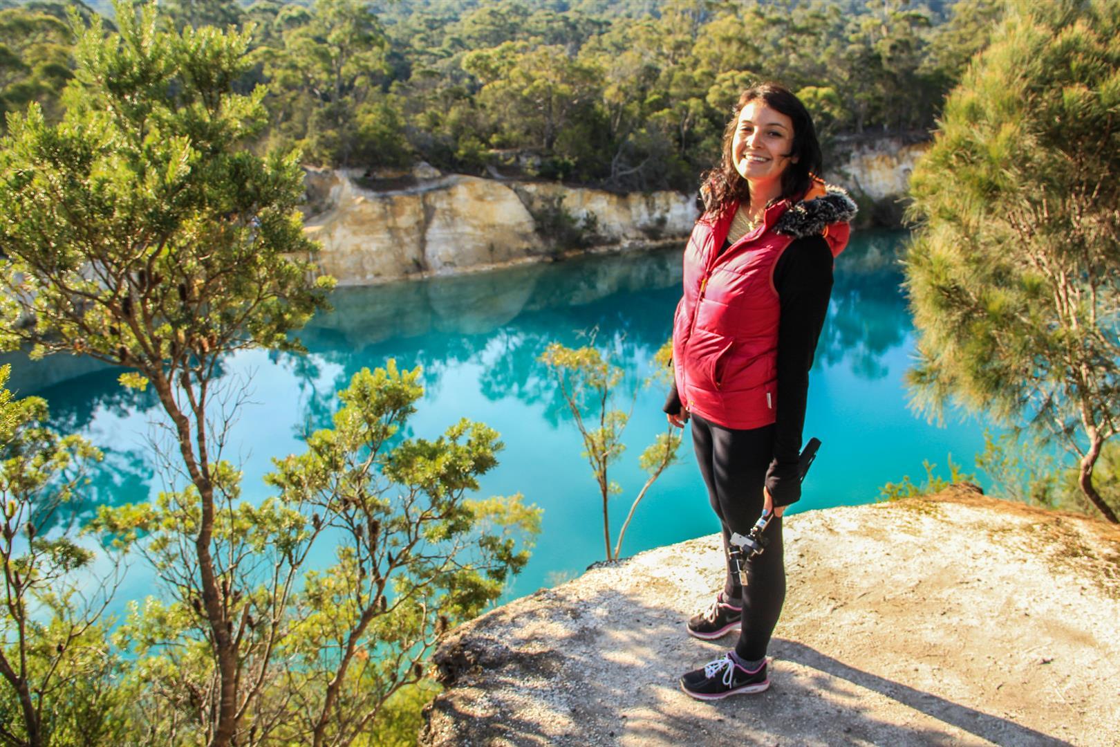 menina na frente de um lago azul