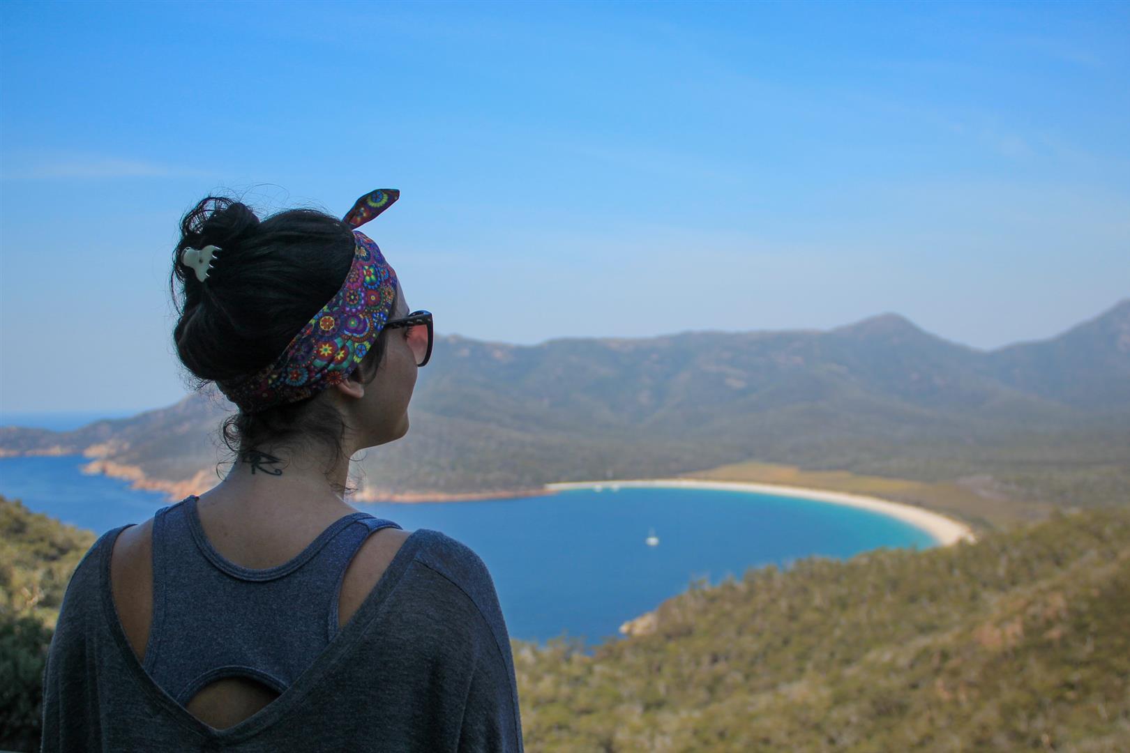 menina olhando para o mar do alto de uma montanha
