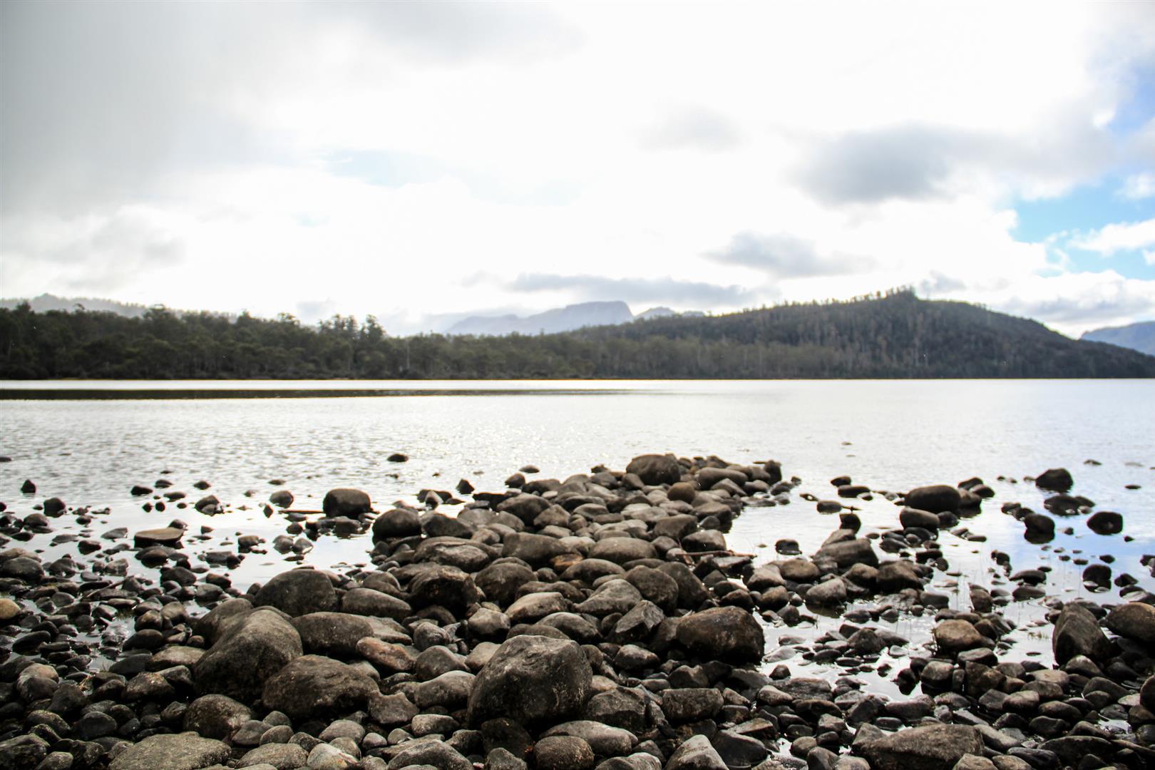 lago com pedras e montanhas