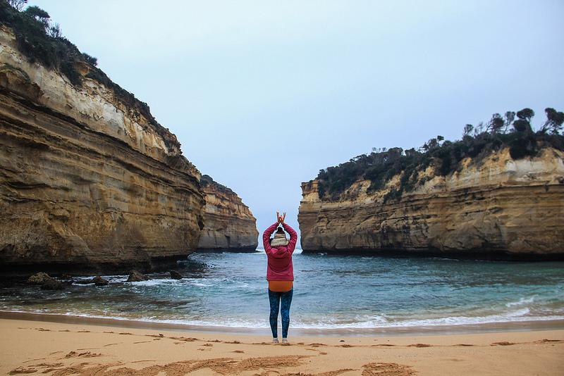 menina fazendo yoga em frente ao mar com pedras