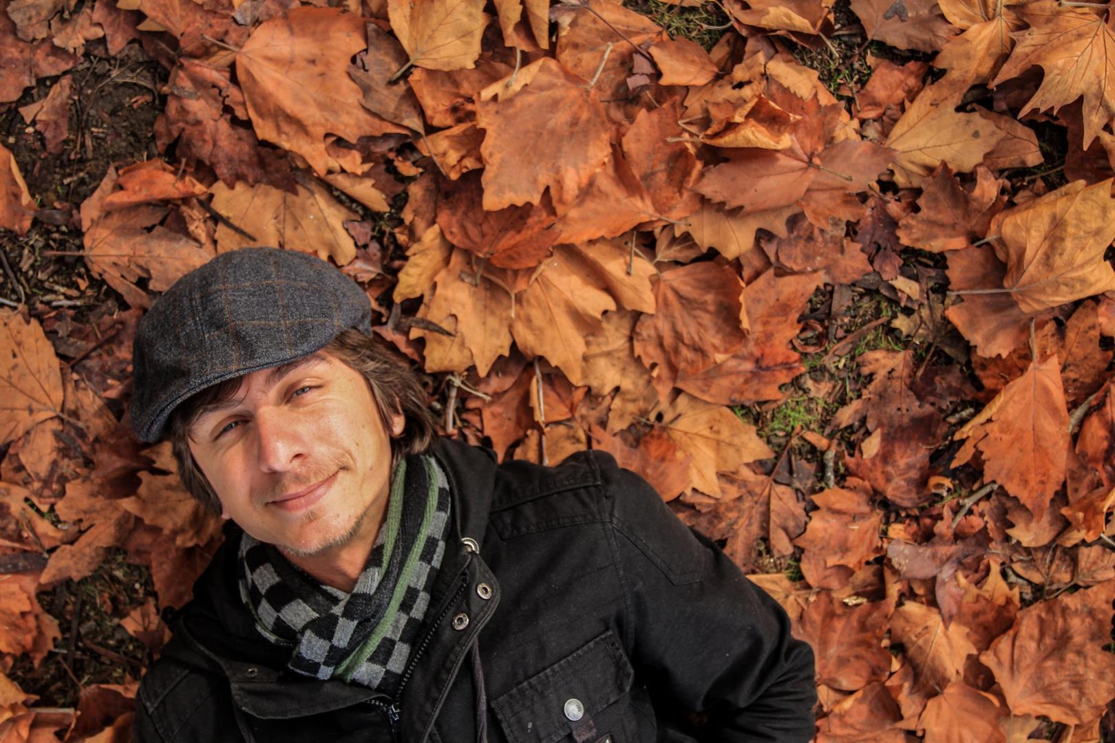 homem deitado em folhas de outono