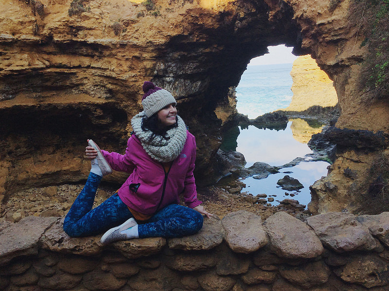 menina fazendo yoga em frente à pedras